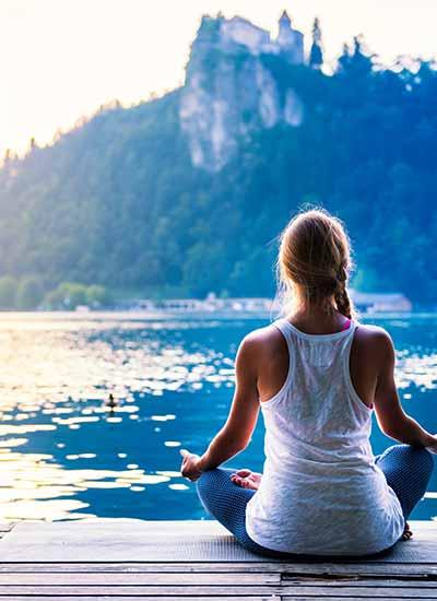 woman sitting by blue lake